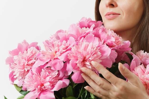 흰색 배경에 격리된 분홍색 모란 꽃다발을 킁킁거리며 들고 있는 부드러운 여성의 자른 사진을 닫습니다. 성 발렌타인 데이, 국제 여성의 날 휴일 개념. 광고 영역입니다.