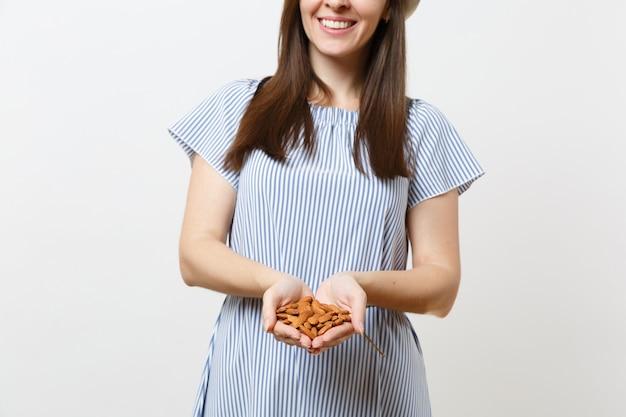 Закройте вверх по обрезанной фотографии женщины, держащей в руках коричневые необработанные орехи миндаля, изолированные на белом фоне. правильное питание, веганское питание, вегетарианское питание, концепция диеты здорового образа жизни. копировать пространство