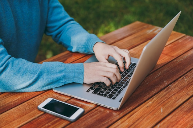 ラップトップを使用して、屋外で作業している都市公園で携帯電話でテーブルに座っている成功した賢い人のビジネスマンや学生のトリミングされた肖像画を閉じます。モバイルオフィスのコンセプト。キーボードの手。