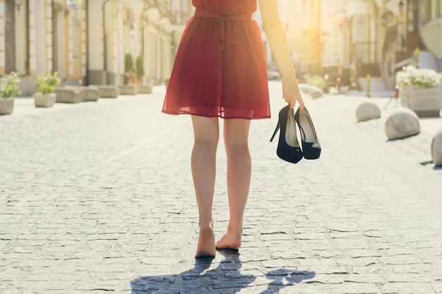 Закройте вверх по обрезанной задней спине за фото взгляда женщины в красном платье, держащей в руках туфли на высоком каблуке. солнечный луч, световые лучи, сияние, солнечные лучи, всплеск, солнечный свет, эффект вспышки, блики, блеск, вспышка.