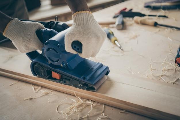 Крупным планом обрезанная шлифовальная машина, используемая для обработки деревянных материалов и превращения их в мебель ручной работы с опилками вокруг.
