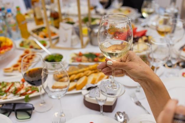 ワインと食べ物のグラスと恋人の手でロマンチックなディナー中にテーブルのトリミングされたショットを閉じます。