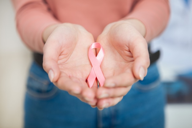 Close up cropped shot of a pink ribbon in the hands of a woman.