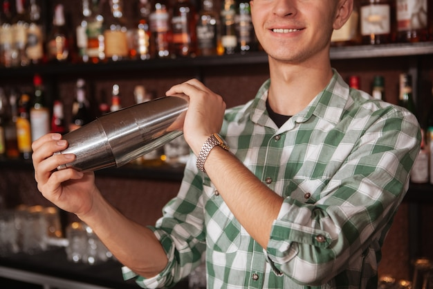 Close up cropped shot of unrecognizable male bartender preparing drink for a customer, using shaker tin