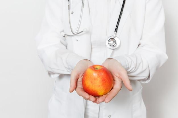 Закройте вверх по подрезанной съемке молодая женщина-врач со стетоскопом, изолированные на белом фоне. женщина-врач в медицинском халате, держа красное яблоко. медицинский персонал, здоровье, концепция медицины правильное питание