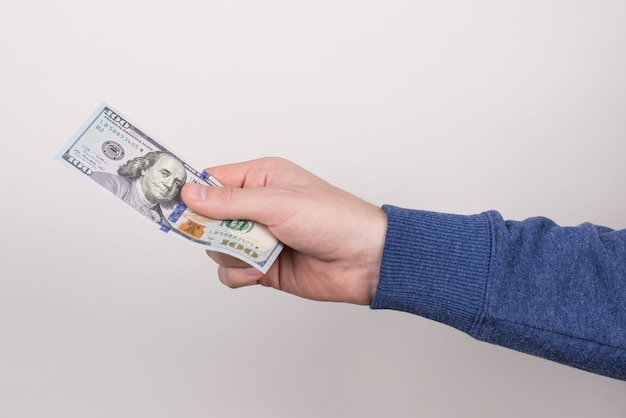 Close-up cropped side profile half turned  of stretching hand holding new usa banknote isolated grey wall