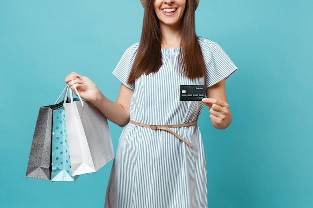 파란색 파스텔 배경에 격리된 은행 신용카드, 쇼핑 후 구매한 패키지 가방을 들고 여름 드레스를 입은 잘려진 웃는 백인 여성을 닫습니다. 광고 공간을 복사합니다.