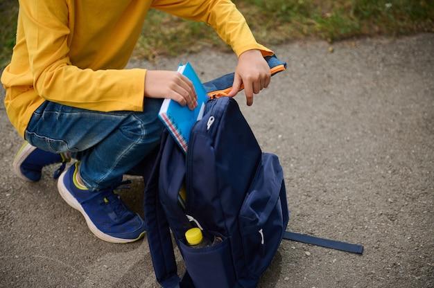 ノートと筆箱をバックパックに入れて、撮影後に家に帰る男子生徒のクローズアップのトリミングされたビュー。学校に戻るコンセプト