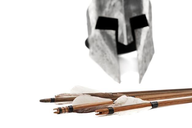 고대 금속은 헬멧과 회색 깃털을 가진 나무 화살의 자른 뷰를 닫습니다.