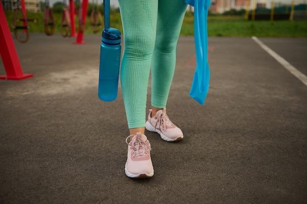 Крупный план. обрезанный вид ног спортсменки в спортивной одежде, держащей синюю пластиковую бутылку с водой и синюю резиновую резинку для фитнеса на фоне спортивного поля