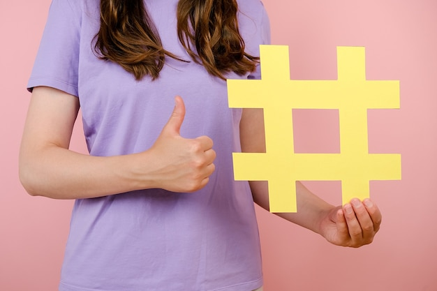 Close up cropped woman blogger holding yellow hashtag sign, giving thumb up for reminder to add tags to your social media marketing posts, isolated on pink background. like to popular blog and trends