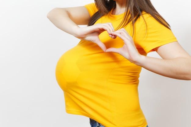 Закройте подрезанного футбольного фаната женщины или игрока с футбольным мячом под желтой формой как беременную с большим животом, изолированным на белом фоне. спорт играть в футбол, здоровье, концепция здорового образа жизни.