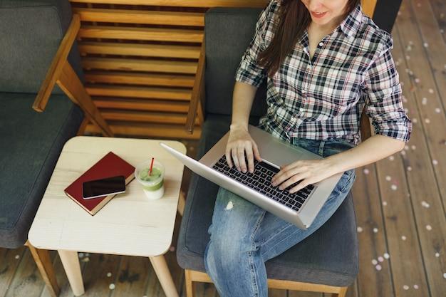 Закройте вверх обрезанной женщины в деревянном кафе уличной кофейни на открытом воздухе, сидя в повседневной одежде, работая на современном портативном компьютере в свободное время. мобильный офис