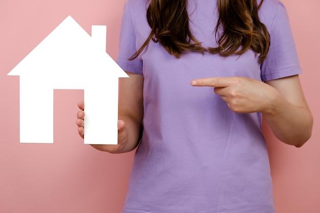 Крупным планом подрезанная молодая кавказская женщина, указывающая на маленький белый бумажный домик, позирует изолированно на стене розового цвета в студии, носит фиолетовую футболку. концепция недвижимости и ипотеки