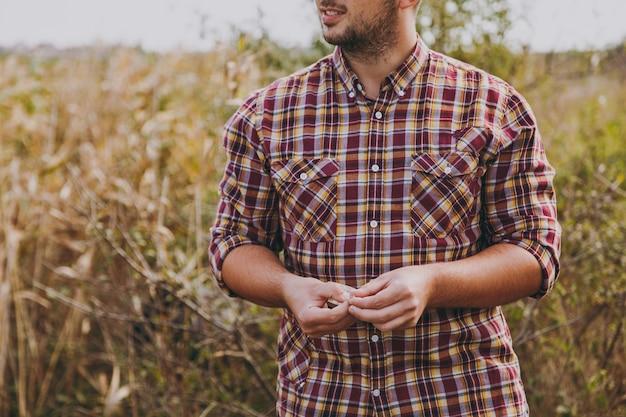 바둑판 무늬 셔츠를 입은 잘린 젊은 남자가 머리를 돌리고 관목과 갈대의 배경에서 낚시를 위해 구더기 미끼를 들고 닫습니다. 라이프 스타일, 어부의 레크리에이션, 레저 개념.