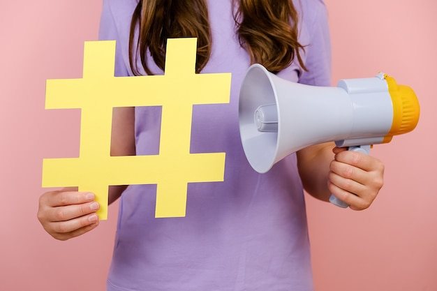 Close up cropped young woman holding yellow hashtag sign and megaphone, label for business, marketing and advertising, isolated on pink background. concept social network monitoring, media measurement