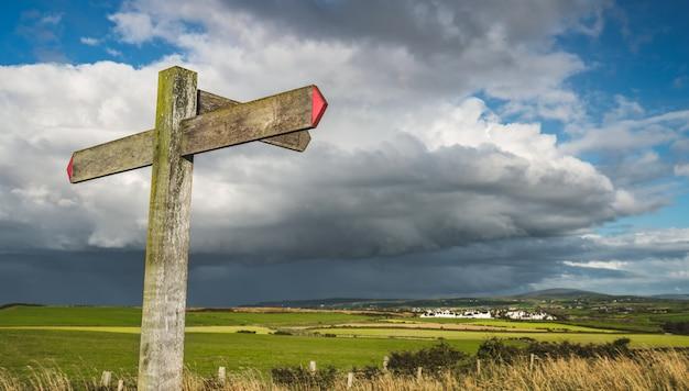 Close-up cross road signpost. rainy sky. ireland.