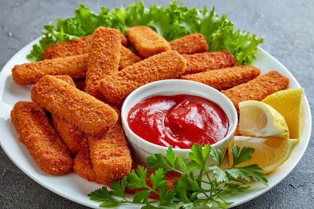 Close-up of crumbed fish sticks served on a white plate with lemon, lettuce leaves and tomato sauce, vertical view from above
