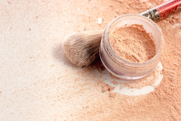 Close-up of crushed mineral shimmer powder golden color with makeup brush