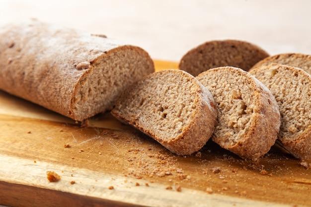 근접 피 각질의 다진 갈색 호밀 빵, 나무 절단 보드에 조각. 수평