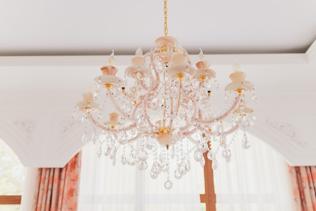 Close up on crystal of contemporary chandelier, is a branched ornamental light fixture designed to be mounted on ceilings or walls.
