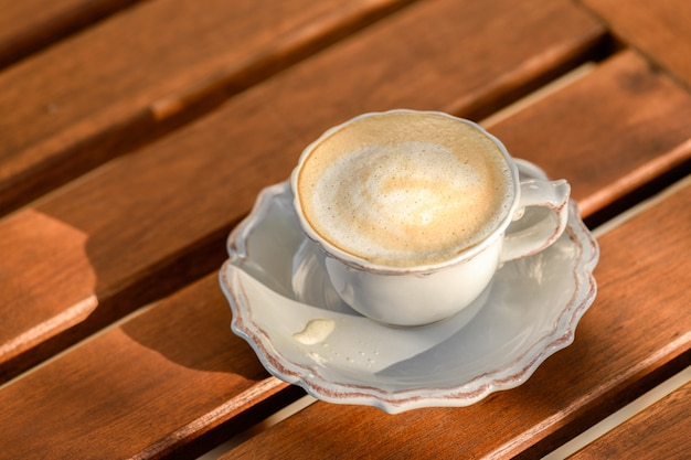 Close up of a cup of cappuccino on a wooden summer table on sunset, enjoying the good moment and time, slow life and digital detox, mental health, me time, gratitude of the day and simple pleasures