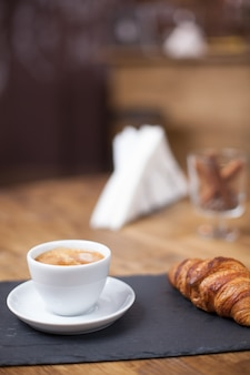 Close up of cup of coffee served with croissant in a cozy coffee shop. coffee aroma.