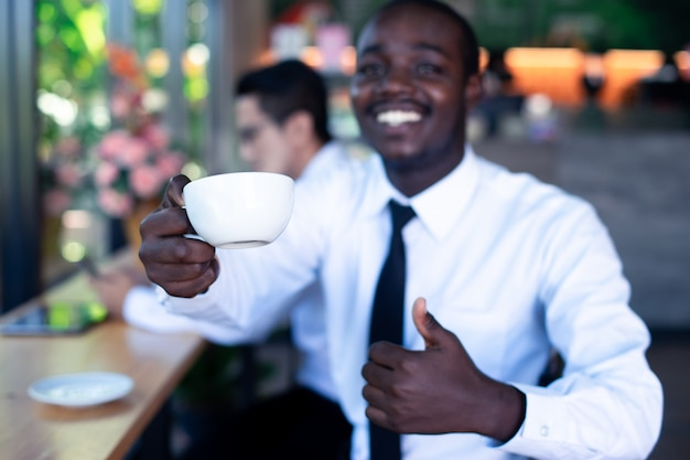 Close up cup of coffee with african and asian business man