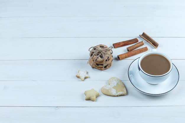 Close-up cup of coffee with cinnamon, different types of cookies on white wooden board background. horizontal