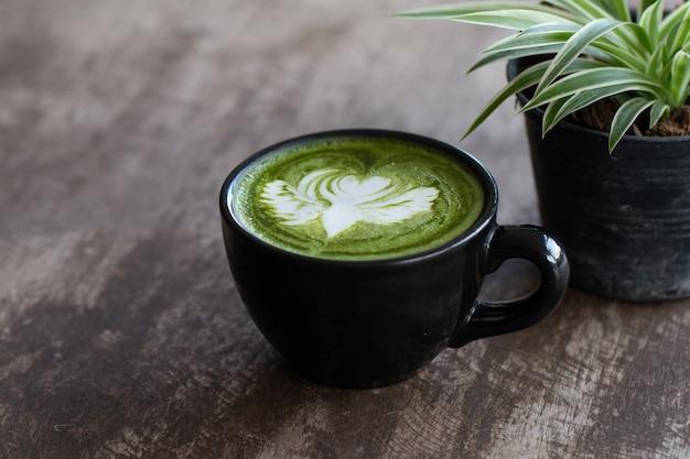 Close up a cup of matcha green tea latte on wooden table background