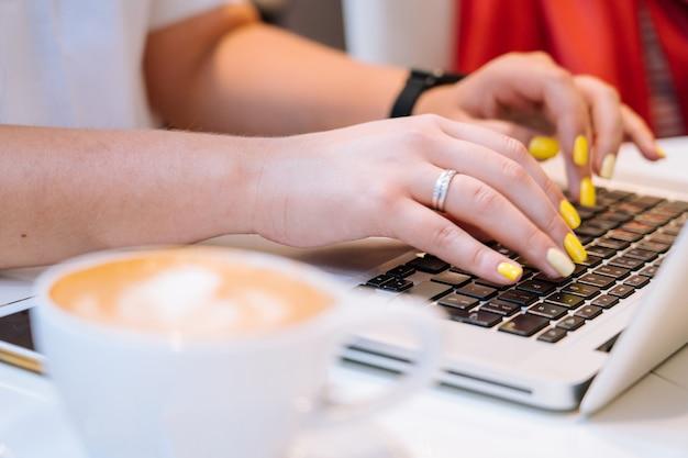 カプチーノコーヒーのカップを閉じて、オフィスのコワーキングに座ってラップトップのキーボードコンピューターで入力している女性に手を差し伸べます。電話、ノート、グラス、コーヒー1杯を備えたデスク。ビジネスコンセプト