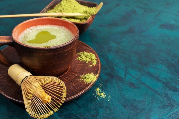 Закройте вверх по чашке зеленого чая matcha, на изумрудном фоне с космосом экземпляра.