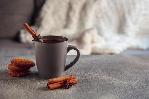 閉じる。灰色と白の背景に分離されたシナモンとクッキーとお茶やコーヒーのカップ。家庭的な雰囲気と快適さ、休日、ロマンチックなデート、冬、クリスマス、新年のコンセプト。