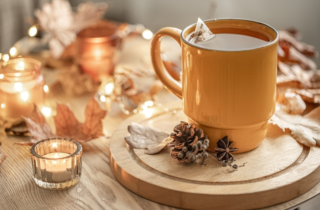 Close-up of a cup of tea among the autumn leaves and candles on a blurred background.
