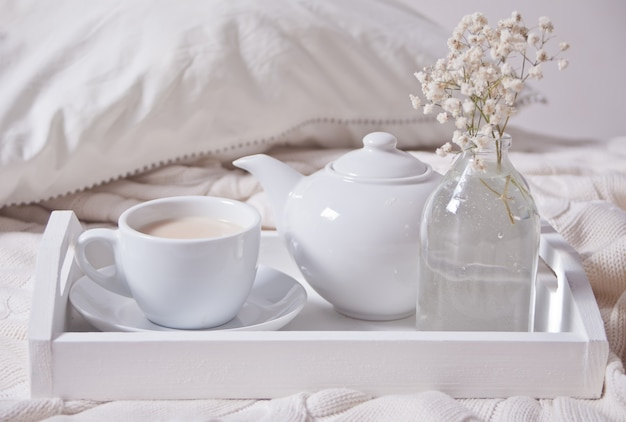 Close up of cup of tea, milk, teapot and bouquet of white flowers on the white tray.
