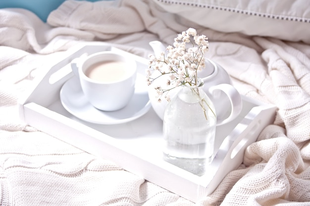 Close up of cup of tea, milk, teapot and bouquet