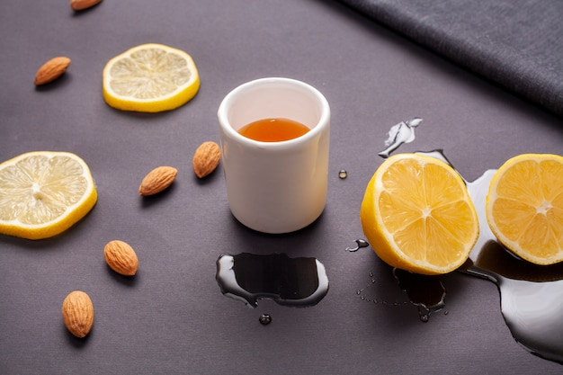 Close-up cup of tea surrounded by lemon slices