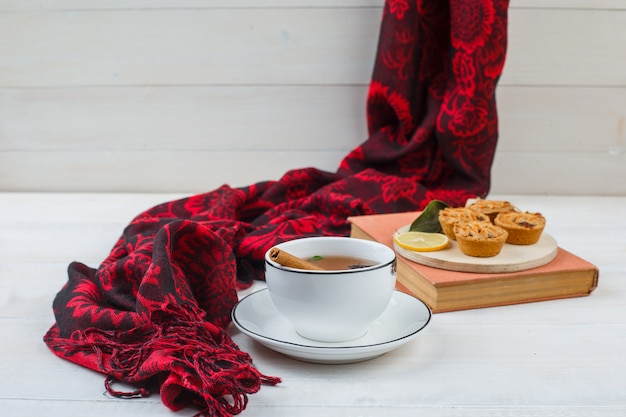 Close-up of cup of tea, white cookies in a plate with red scarf and a book