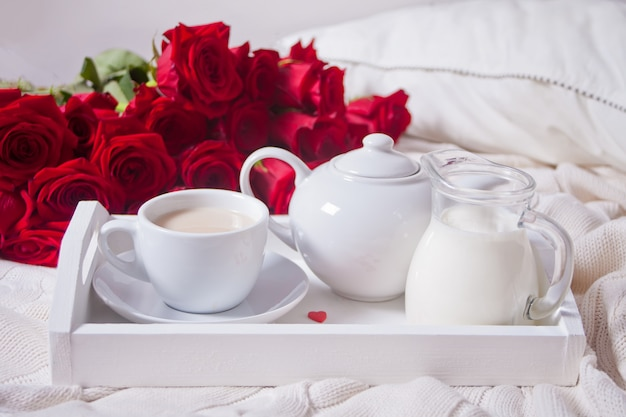 Close up of cup of tea with red roses on the white tray