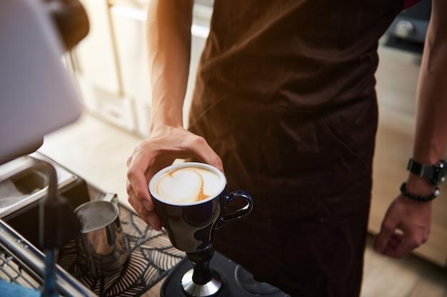 閉じる。男性のバリスタの手でカプチーノとカップ。コーヒーショップのバーカウンターの後ろのバリスタ