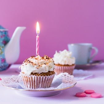 Close-up of cupcake with burning candle on birthday