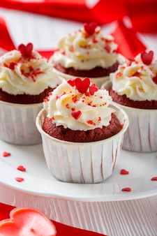 Close-up of cupcakes with heart-shaped sprinkles and candle