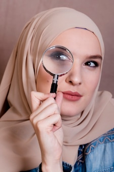 Close-up of a curious muslim woman looking through magnifying glass