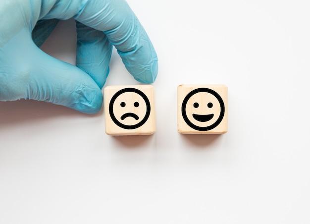 クローズアップの顧客は、木製の立方体、サービスの評価、満足度の概念のスマイリーフェイスと悲しい顔のアイコンを選択します。