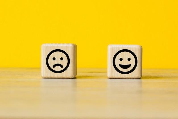 Крупным планом клиент выбирает смайлик и значок грустного лица на деревянном кубе, рейтинг обслуживания, концепцию удовлетворения.