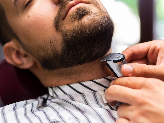 Close-up customer getting his beard trimmed