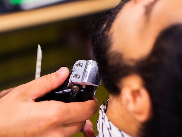 Close-up of customer getting his beard trimmed