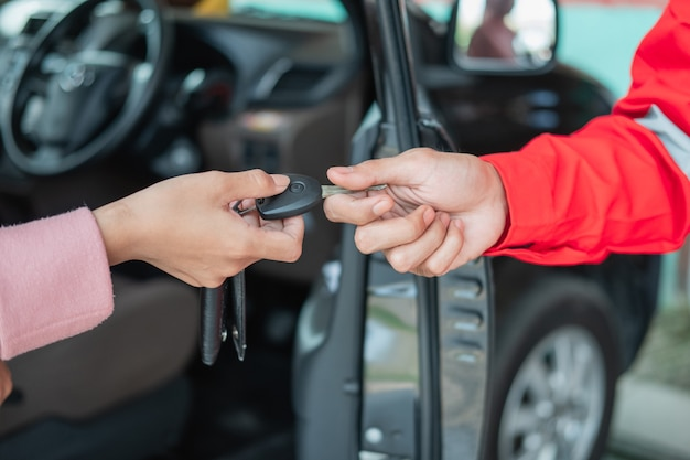 Close up of customer hand giving car keys to mechanic with workshop background