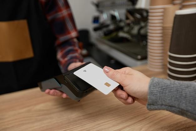 클로즈업, 고객의 손이 nfc 터미널 근처에 신용 카드를 들고 있습니다. 바리스타는 커피숍에서 pos 기계를 통해 신용 카드로 결제를 수락합니다.