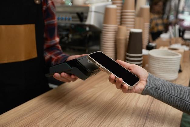 클로즈업, 고객이 nfc 터미널 근처에 전화를 들고 비접촉 모바일 결제를 합니다. 바리스타는 카페에서 포스 머신을 통해 휴대전화로 결제를 받습니다.